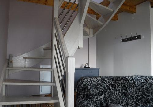 Vue de l'escalier situé dans le coin salon, menant aux chambres du gîte Lou Saltret en Lozère