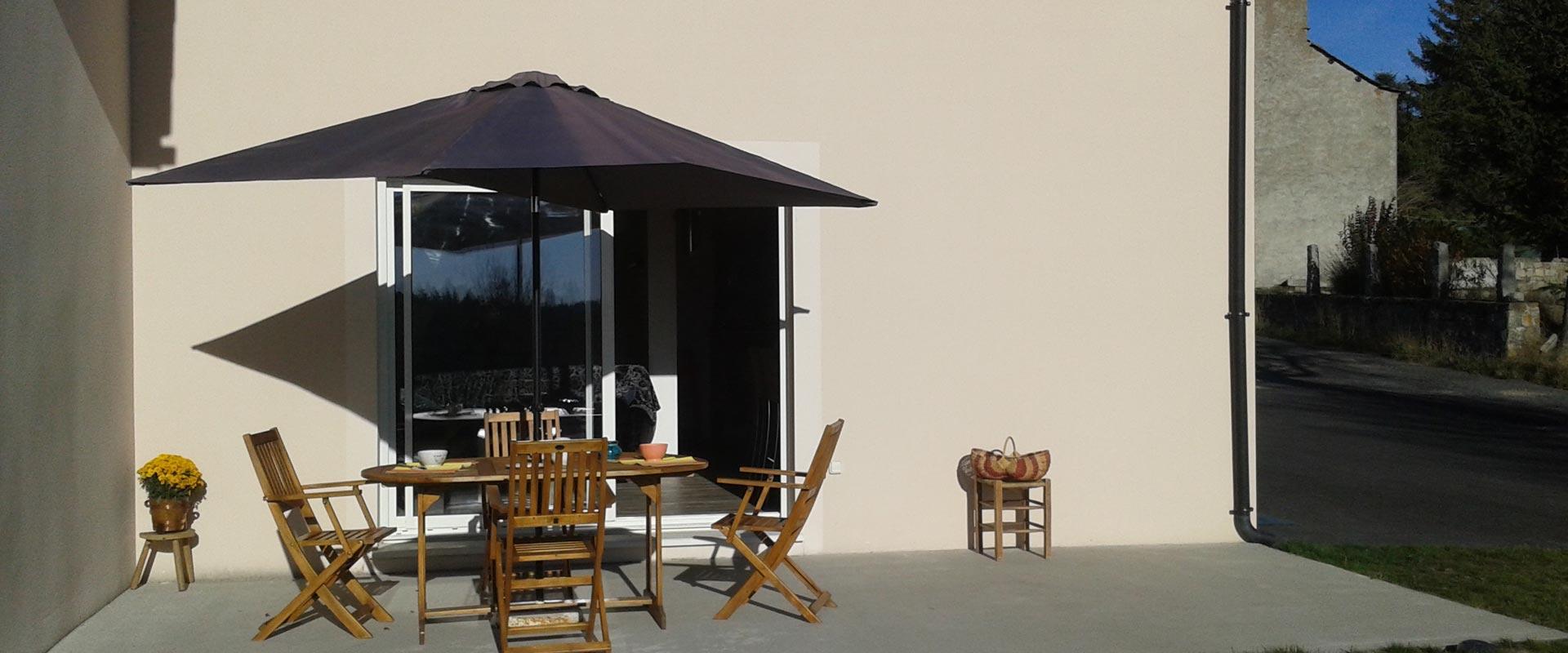 Aménagement extéreur, la terrasse avec salon de jardin teck + parasol du gîte Lou Saltret en Lozère